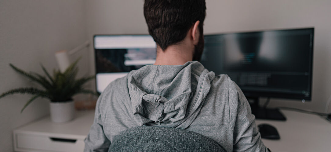 A male with a grey hooded long sleeve sitting at his desk using JetStream DataFile Transfer services